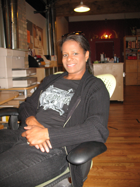 Debi Thomas sitting and smiling in a photo for the Manleywoman Skatecast, a figure skating podcast