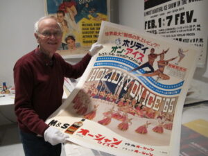 Roy Blakey holding up a 1965 Holiday on Ice poster in a photo for the manleywoman skatecast, a figure skating podcast