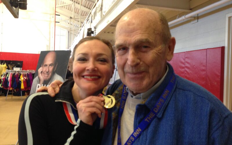 Allison holding a gold medal next to Dick Button, for the manleywoman skatecast, a figure skating podcast