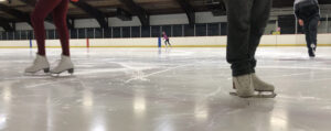 image of skater's boots and feet on an ice surface, for the manleywoman skatecast, a figure skating podcast