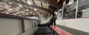 Allison sitting in the hockey box at ice rink with legs up on boards in a photo for for the manleywoman skatecast, a figure skating podcast